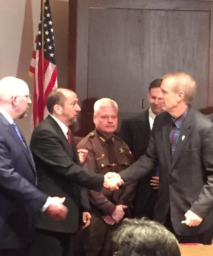 At the signing of executive order establishing criminal justice commission, Governor Rauner greets Mike Torchia, director of Court Services for Sangamon County Adult Probation.  (Photo by TASC.)